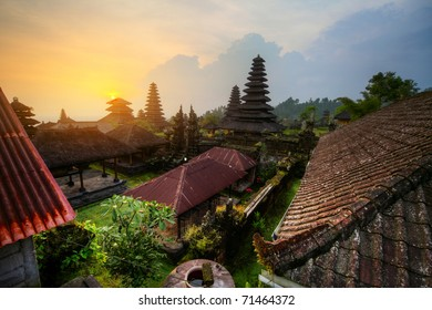 Yard with green trees and buildings of indonesian old temple Pura Besakih at sunset light. Bali. HDR image