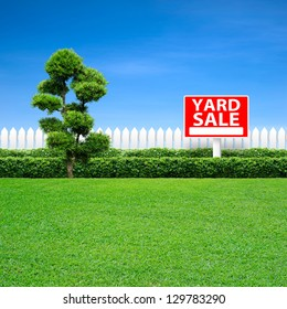 Yard sale sign and white fence on green grass