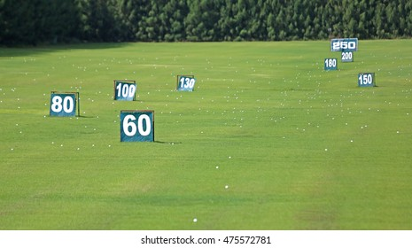Yard signs in driving range and golf ball in golf course
