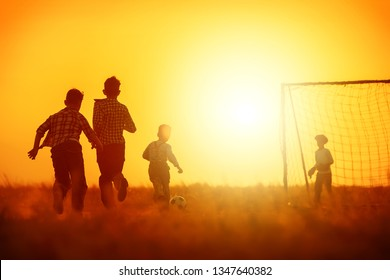 Yard team of football players against the backdrop of the gate in the field on the sunset