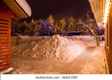 yard in winter with lots of snow lighted by christmas lights