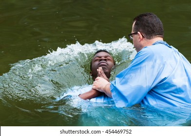 Yardenit, Israel - 29 December 2012: a man gets baptised in the Jordan River, during a mass celebration. The man's head splashes into the water as he dives.