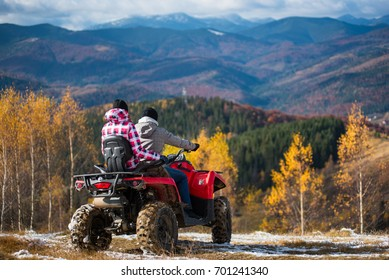 Yaremche, Ukraine - October 30, 2016: Rear view of couple in winter clothing on a quad bike atv at the hill enjoying beautiful autumn landscape mountains and forests. Sunny day