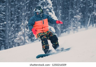YAREMCHE,UKRAINE-20 MARCH,2018: Snowboard athlete rides on board on track in snow park.Snowboarder goes fast down the hill in Bukovel Winter Park
