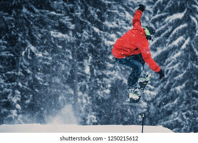 YAREMCHE,UKRAINE-20 MARCH,2018: Young snowboarder performing trick on kicker ramp in winter sports park.Snowboard athlete jumps high in the air on competition in Bukovel Snow Park