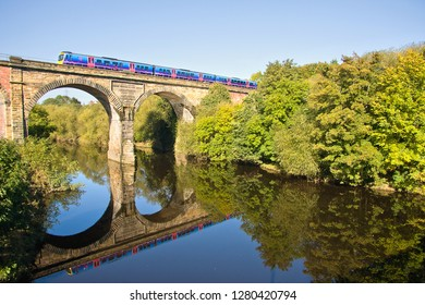 YARM, COUNTY DURHAM, UK, - OCTOBER 9, 2012: Perfectly reflected in the waters of the River Tees, a First TransPennine Class 185 works a Middlesbrough to Manchester Airport service over Yarm Viaduct.