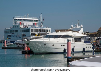 Yarmouth Harbour, Isle of Wight, UK. 2021.  Luxury cabin cruiser and a ro ro ferry alongside the  harbour at Yarmouth, Isle of Wight.