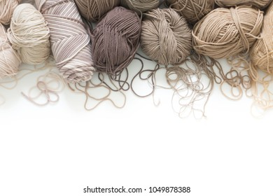 The yarn is beige, brown, gray and white. Knitting needles, scissors, knitting, knitted fabric.