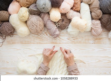 The yarn is beige, brown, gray and white. The background is aged wood. Knitting needles, scissors, coffee, knitting, knitted fabric.