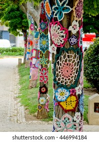 Yarn bombing.  A tree dressed with knitted colorful wool. European park.