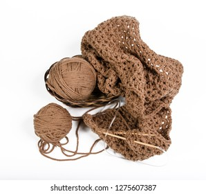 yarn and knitted fabric in a wicker basket on a white background