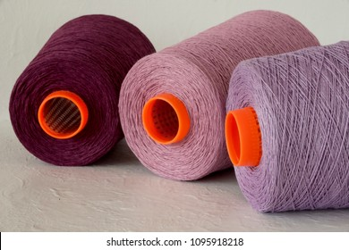 Yarn on cones in pink purple colors, wool, cotton, linen textile