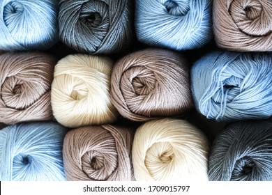 Yarn skeins background. Plenty of brown, milk and blue skeins of yarn for knitting