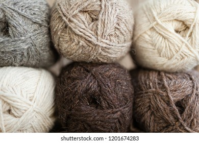 Yarn skeins for handmade. Beige, brown, gray and white balls of yarn. Wooden background, natural wool knitting background