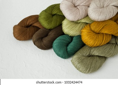yarn skeins set in green and brown colors on white background, linen, cotton, craft, wool, yarn collection.