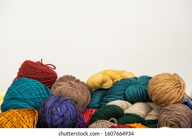 Yarn stash in a brown basket with white background.