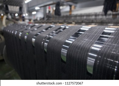 Yarn thread lines on the weaving loom machine. A loom machine for clothing or woven label. Weaving machine for garment industry. Weaving loom in textile factory.