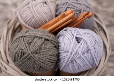 Yarns in basket with crochet hooks in harmonious colors. knitting, crocheting supplies.