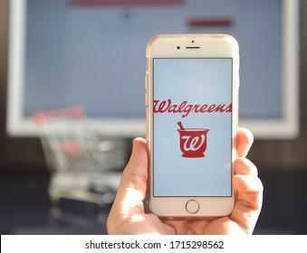 Yaroslavl, Russia - 26 April 2020: Human hand holding smartphone with Walgreens logo.
