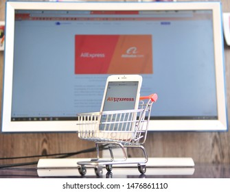 YAROSLAVL, RUSSIA - AUGUST 12, 2019: Smartphone with Aliexpress logo and shopping cart with computer screen on background. Aliexpress online retail service based in China.