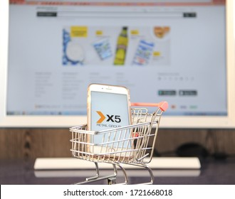 Yaroslavl, Russia - May 2, 2020: Smartphone with X5 Retail Group logo in mini shopping cart with PC on background