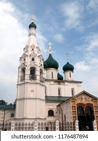 Yaroslavl (Russia), view on the church of St Elijah the Prophet (Ilyi Proroka). Blue sky with white clouds. White stone church with green cupolas and golden crosses. Vertical.