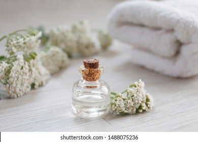 yarrow essential oil container with yarrow flowers and on wooden background, shallow dof, vertical