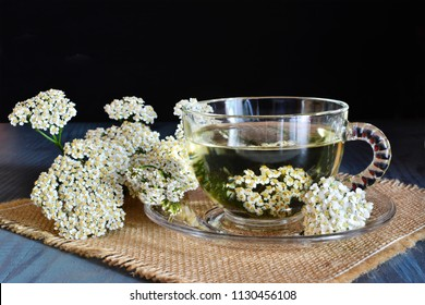 Yarrow medicinal tea in glass cup and yarrow flowers on wooden table over dark background (Achillea millefolium)