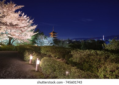 Yasaka Pagoda lit up at night in the spring, with Kyoto Tower in the distance.