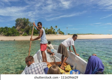 YASAWA ISLANDS, FIJI, AUGUST 25 2017: Group of Fijians travelling from Yasawa island Wayalailai to an uninhabited island to hunt for food. The pole is used to navigate through coral reef at low tide.
