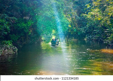 YASUNI NATIONAL PARK, ECUADOR - JUNE 22, 2018: A group of tourists in a traditional wooden paddle canoe on a adventure with sun rays shining through the tree canopy of the Amazon Rainforest.