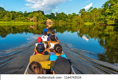 YASUNI NATIONAL PARK, ECUADOR - JUNE 25, 2018: Transport in canoe along the rivers of the Amazon River Basin inside the Yasuni National Park with a view of a lodge in traditional style, Ecuador.