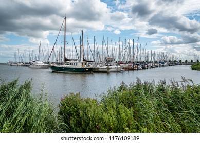 Yatchs moored in the marina of Volendam. Sunny day with beautiful white clouds
