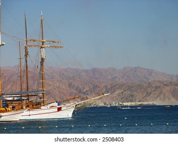 yatchs at the sea with desert mountains in the background