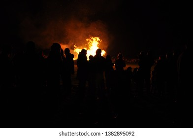 Yateley, UK - November 5 2011: Local residents stand in front of a bonfire on Guy Fawkes night.