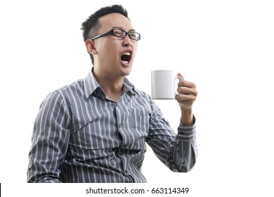Yawning Asian male holding a cup of coffee isolated on white background