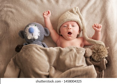 Yawning baby with a knitted cap  with bobble and  a toy side by side covered with a gray blanket.