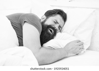 yawning bearded man feel sleepy and tired in bedroom, early morning wake up.