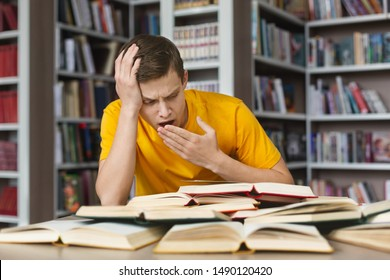 Yawning caucasian student sitting in front of open books, making homework in library