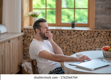 Yawning. Dark-haired handsome man sitting at the table and yawning
