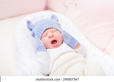 Yawning little baby wearing knitted blue hat with ears and mittens lying in beautiful cradle. Security and childcare concept