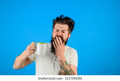 Yawning man. Awaking. Yawning man with sleepy face try to awake with cup of coffee. Tired guy hold coffee mug. Man hold mug with coffee. Sleepy man holds cup of coffee. Morning refreshment.
