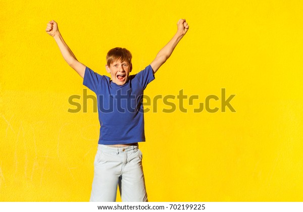 Yay! The happiness beautiful boy in casual clothing, looking at camera, celebrates the victory. Isolated studio shot on yellow background