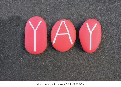 YAY word composed with red colored stones over black sand