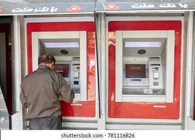 Yazd, Iran - April 22, 2017: An elderly Iranian man uses an ATM to withdraw cash from a national payment card of Iran.
