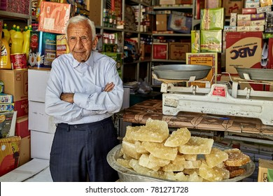 Yazd, Iran - April 22, 2017: One unknown elderly grocer stands with his arms crossed near the pelvis with yellow rocky sugar.