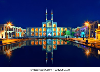 YAZD, IRAN - APRIL 7, 2018: Amir Chakhmaq Mosque and its reflection in the pool, at the twilight, in Yazd, Iran. The mosque, built in 15th century, is one of the most significant historical buildings.