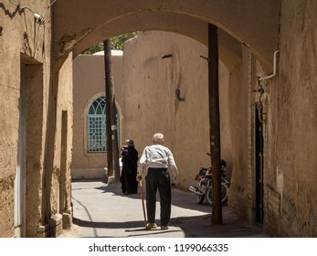 YAZD, IRAN - AUGUST 10, 2015: Iranian seniors, one old man and one old woman, walking in one of the streets of the old town of Yazd, one of the main cities of central Iran