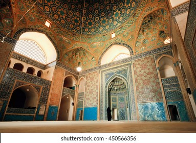 YAZD, IRAN - OCT 19: Wide colorful hall of ancient mosque and lonely woman praying inside on October 19, 2014. With population of 270.600 families, Yazd is centre of Persian architecture