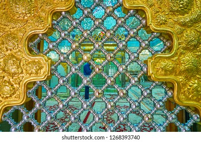 YAZD, IRAN - OCTOBER 18, 2017: The view through the shining metal lattice of the Persian screen to the men's praer hall of Imam Zadeh Jafar Shrine, on October 18 in Yazd.
